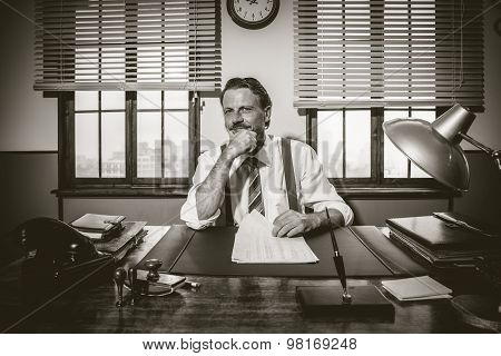 Confident Businessman Working At Desk With Hand On Chin