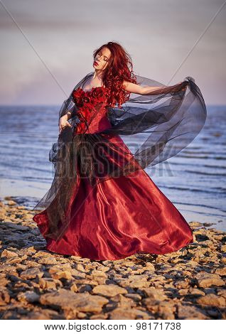 Beautiful Young Woman In Red Dress Standing On Sea Coast