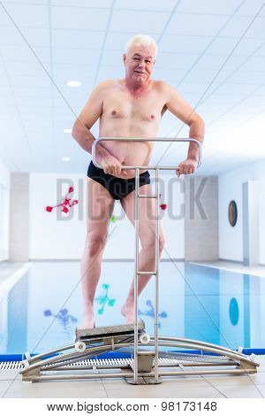 Senior man in underwater gymnastics therapy with sliding machine