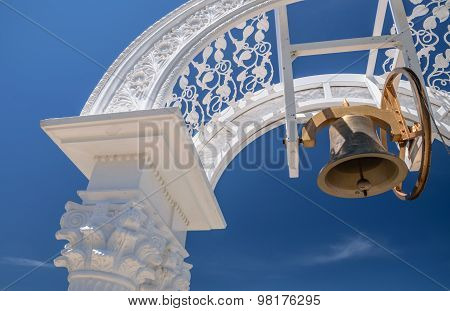 Bell Hanging In Arch Over Blue Sky Background