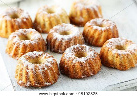 Bundt Cakes On Cutting Board On White Wooden Background