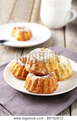 Bundt Cakes On Plate On Grey Wooden Background
