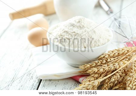 Bowl Of Wheat Flour With Eggs And Whisk On White Wooden Background