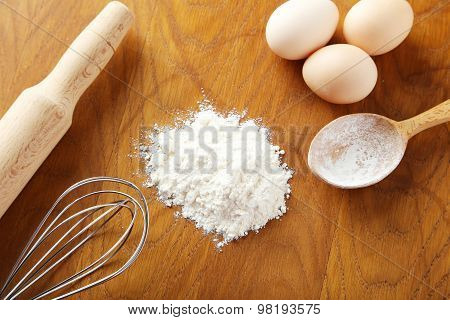 Heap Of Wheat Flour With Eggs, Rolling Pin And Spikelets On Brown Wooden Background