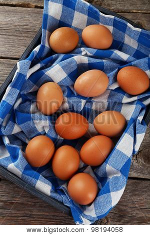 Chicken eggs in tray on grey wooden background