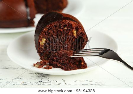 Slice of chocolate pie on white plate on white wooden background