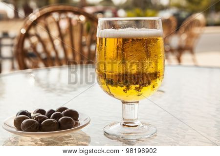 Misted glass of beer with olives on a glass table.