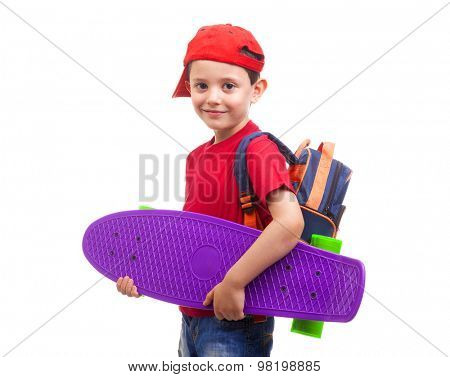 Smiling schoolkid standing with skateboard and backpack on white background