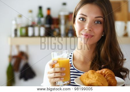Young woman with glass of juice and cakes .