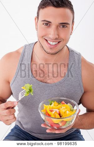 Handsome young guy is eating tasty food