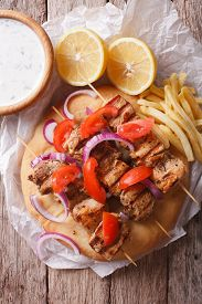 picture of souvlaki  - Greek souvlaki kebabs with vegetables and french fries on pita bread close - JPG
