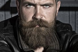 picture of long beard  - Portrait of handsome sullen unshaven male with long beard and handlebar moustache in black leather jacket sitting looking forward on workshop background horizontal picture - JPG
