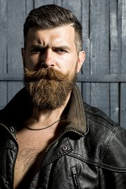 stock photo of long beard  - Portrait of sexy brutal unshaven guy with long beard and hendlebar in brown leather jacket and chain looking forward standing on grey wooden background vertical picture - JPG