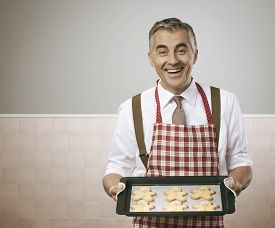 foto of gingerbread man  - Smiling vintage man in apron cooking delicious gingerbread men cookies on a baking tray - JPG