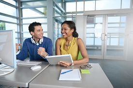 image of coworkers  - Couple of business coworkers collaborating on a project in a bright glass office - JPG