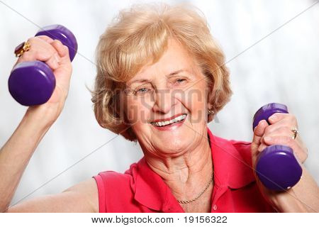 A picture of a senior lady working out with weights over white background