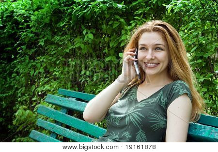 Beautiful young woman talking at the phone