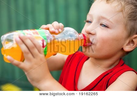 Little boy drinking unhealthy bottled soda