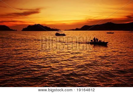 Boat with people in sunset of tropical sea. Siam bay. Province Trat. Koh Mak island. Kingdom Thailand