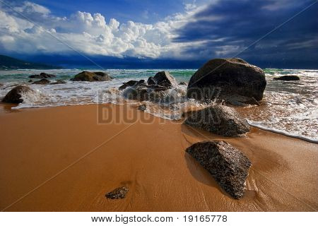 Big stones on the sand tropical beach in bad weather. Phuket island. Andaman sea. Kingdom Thailand