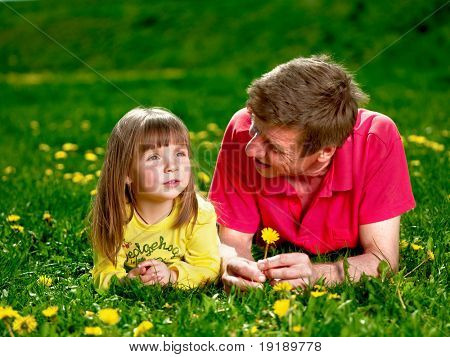 grandfather with granddaughter on meadow