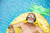 Closeup of caucasian senior man in the pool with headphones poster