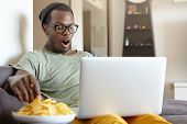 Dark-skinned Guy Watching Movies At Home Over Notebook Eatting Crisps Being Shocked By Plot. Restful poster
