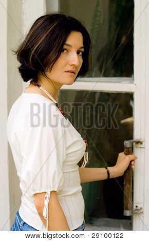 attractive woman opening the door of an old private residence