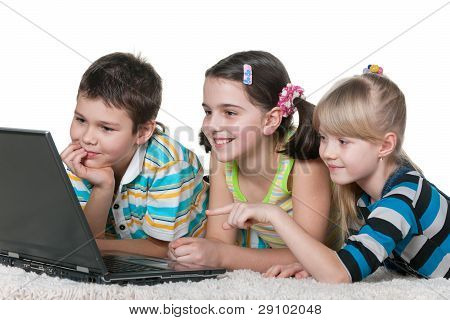 Three Kids Reading Internet Information Using A Laptop
