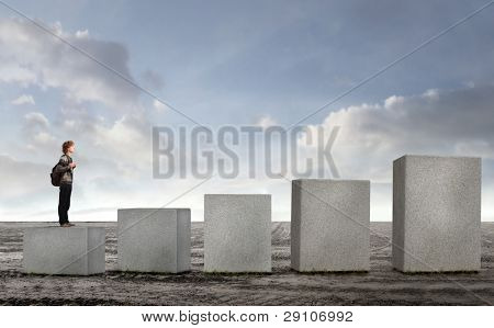 Student on the lowest of stone cubes in ascending order