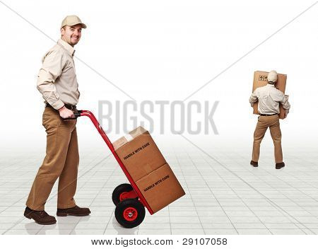 smiling young delivery man and boxes