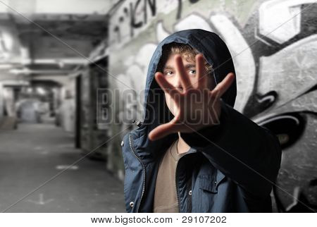 Young man on a city street hiding behind his hand