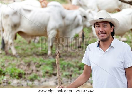 Cowboy portrait in a farm with cattle at the background