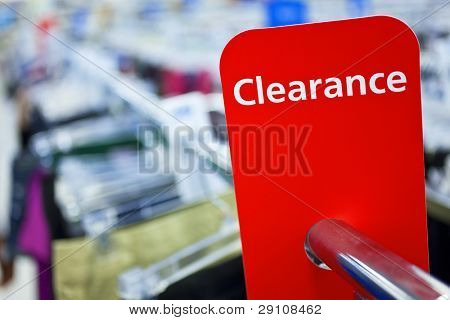 A red sale clearance sign on rail of clothes in a shop
