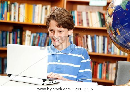 Cute little boy using a netbook computer in the school library.