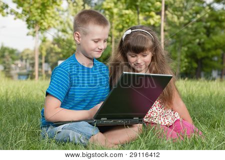 With A Laptop On The Grass