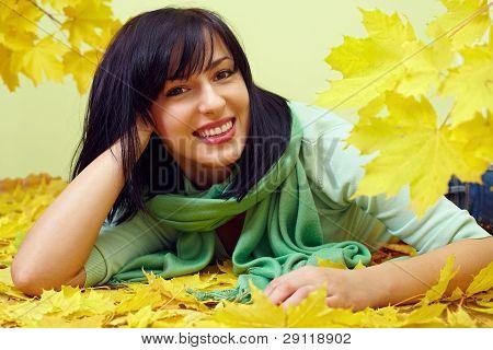 Attractive Smiling Brunette Woman Lying In Yellow Fallen Leaves, Wearing Green Scarf