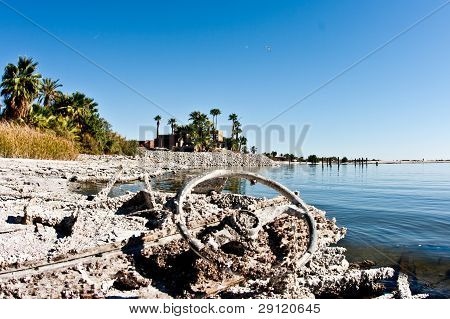 Ship's wheel and other remains of a heavily decayed boat on the beach of the Salton Sea