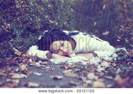 Místico Lonely Girl Angel tumbado en el suelo entre los caídos, hojas y plumas