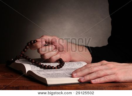 Hands holding wooden rosary over open russian holy bible on grey background