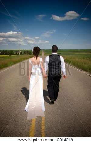 Bride And Groom Walking Down Long Road Hand In Hand