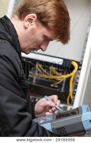 Technician Adjusting Telecom Instrument