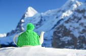 Tea pot in the knitted cap on the snow against mountain peak