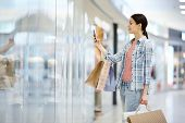 Content Attractive Young Woman With Pony Tail Holding Shopping Bags And Photographing Shop-window On poster