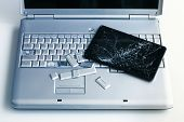 A Silver Laptop With A Broken Keyboard And A Tablet With A Cracked Display. A Close-up Picture Of Pa poster