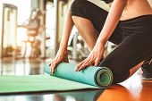 Close Up Of Sporty Woman Folding Yoga Mattress In Sport Fitness Gym Training Center Background. Exer poster