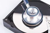 Technology And Data Recovery Concept, Stethoscope On Old Dusty Disassembled Hard Drive From The Comp poster