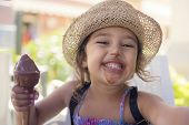 Little Girl With A Straw Hat And A Summer Dress Enjoys The Summer Heat Eating A Refreshing Ice Cream poster