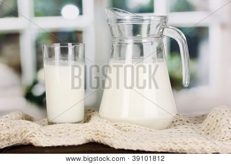 Pitcher and glass of milk on crewnecks knitwear on wooden table on window background