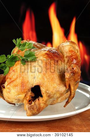 Roasted whole chicken on a white plate on wooden background close-up